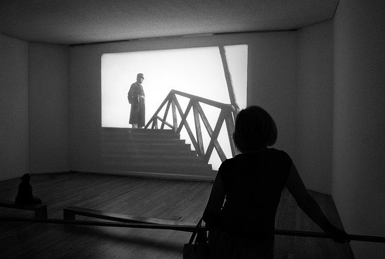 Projecção de um filme, com um soldado na tela, uma espectadora em primeiro plano e outra num intermédio, formando um triàngulo.