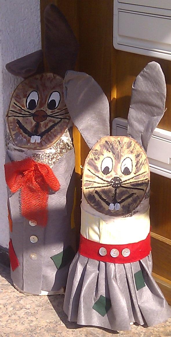 Bild: Osterhase und Osterhäsin, aus Holzstämmen mit aufgemalten Gesichtern, Kleidung und Stoff-Ohren.
