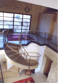 Photographié en grand angle, le grand escalier de la nef accède aux chambres à l'étage et, dehors, au studio indépendant, au parking voitures et au logement du gardien