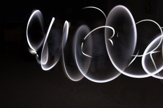light patterns made using flashlights in the dark and a long camera shutter speed