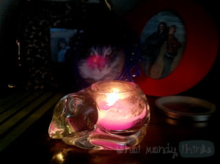 """What Mandy Thinks: Image of a lit candle in darkness: """"I might have several of these glass kitties."""""""