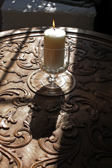 candle with essential oils on carved wood tabletop, afternoon sun by LeAnn B. at home for l&l