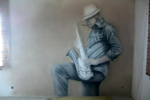 Malowanie na ścianie obrazu przedstawiającego saksofonistę, pokój jzzowy, mural czarno=biały, cena murala