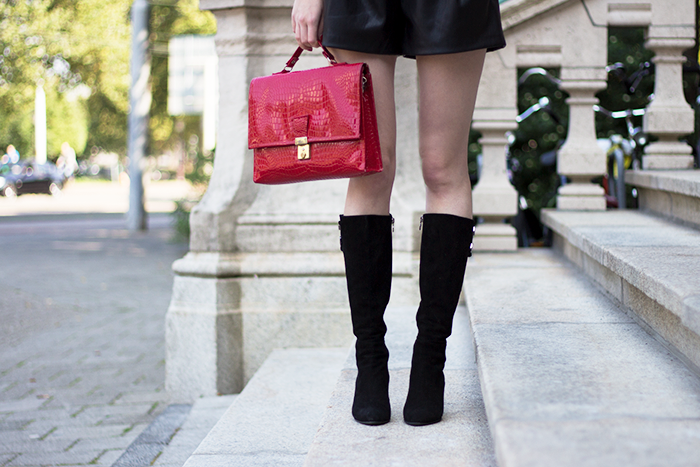 Faux leather shorts, black suede boots and a red purse
