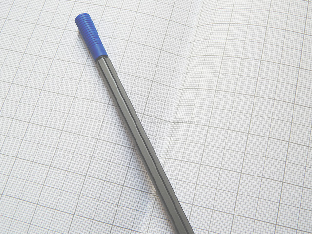grid paper with blue and black pen on top