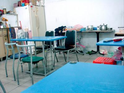 店景內觀,藍色塑膠桌子與白牆空間,牆邊堆有雜物,很平常的店