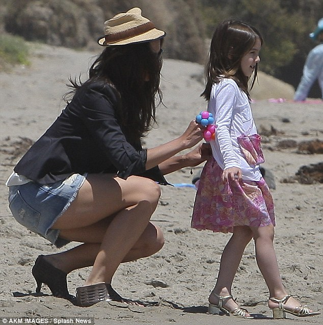 So that's where she gets it from! Suri Cruise and Katie Holmes sink into the sand in their heels at beach party