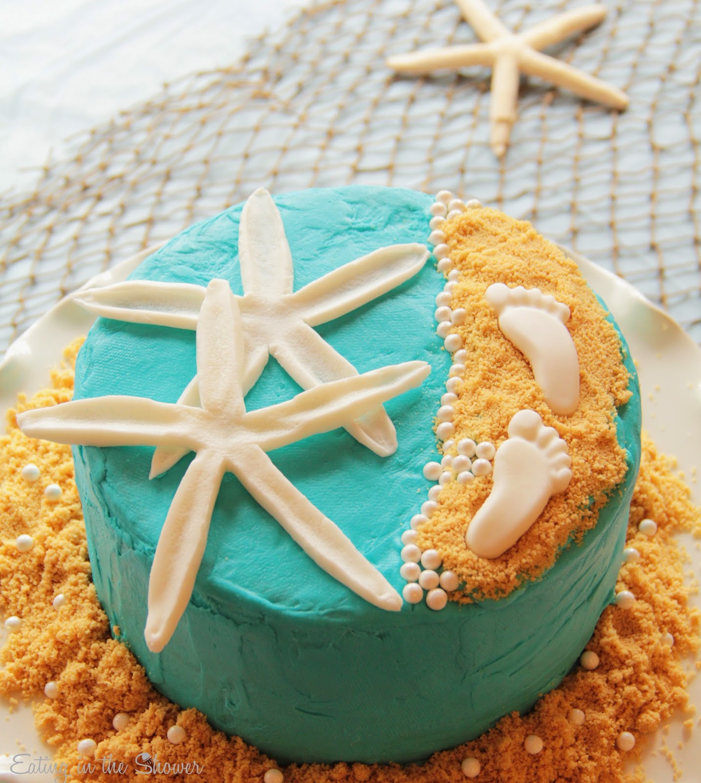 Adorable Beach theme baby shower cake with starfish and baby footprints