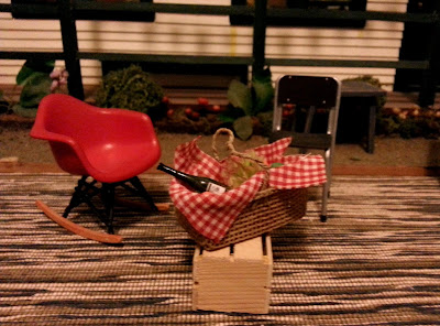 Two modern dolls' house miniature chairs and a picnic basket full of food, on a dining table in front of a dolls' house miniature school.