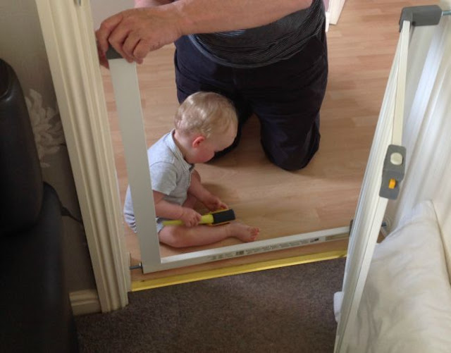 baby sitting on floor holding tape measure next to baby gate