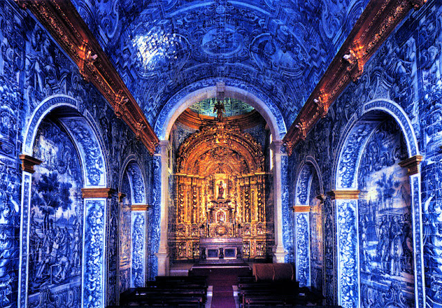 The magnificent interior of the church of São Lourenço is covered in vibrant blue and white azulejo tiles that Portugal is renowned for. Head to the altar to see the gilded wooden altarpiece—incredibly striking! Photo: Grufnik.
