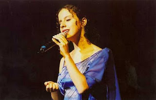 Sara cantando, usando um elegante vestido azul de cortes assimétricos, com bordados e detalhes em strass.