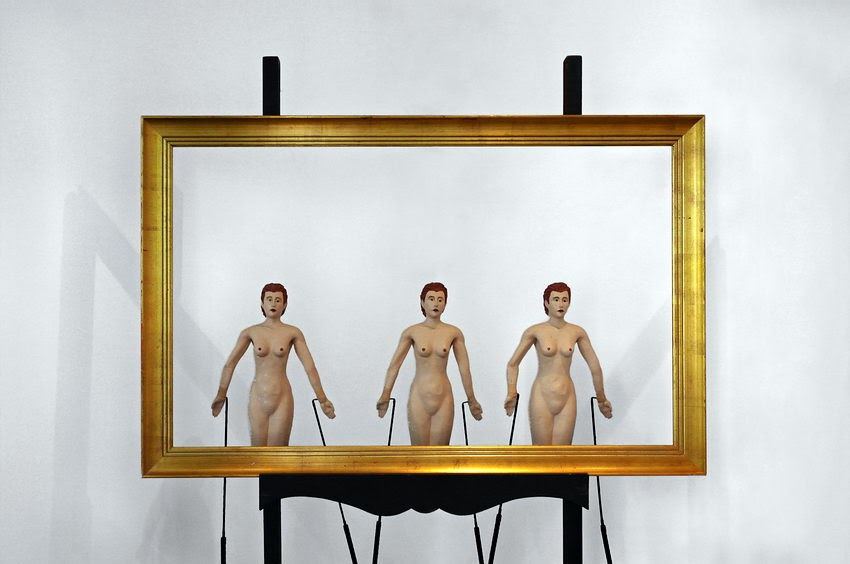 Foto de uma moldura dourada em cima dum suporte com três marionetas femininas, nuas por detrás, como se as mesmas fizessem parte do quadro