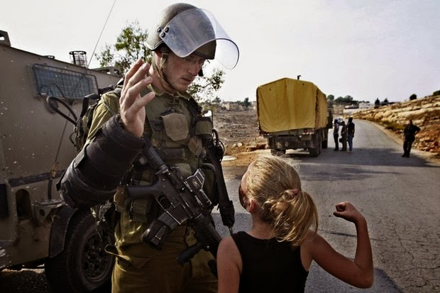A Palestinian girl raises her fist against an Israeli soldier