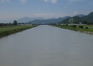 View of the distant Alps from a bridge over the river Rhein, Austria
