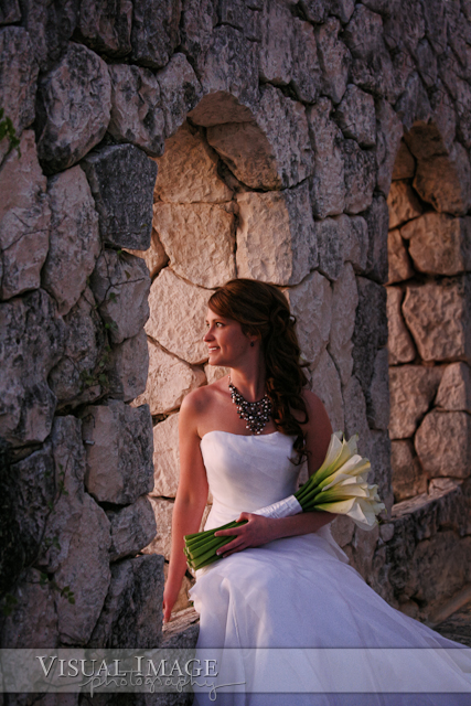 Portrait of bride sitting on stone wall with sunset coming through window