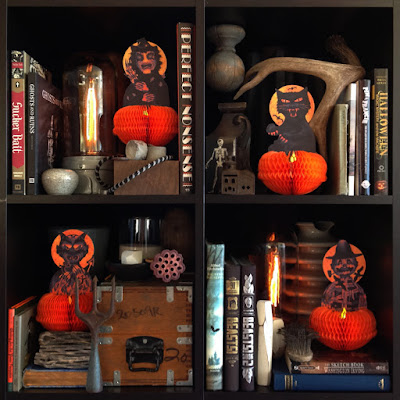 Honeycomb decorations (witch, scarecrow, black cat, and devil) on a shelf with various creepy and spooky books.