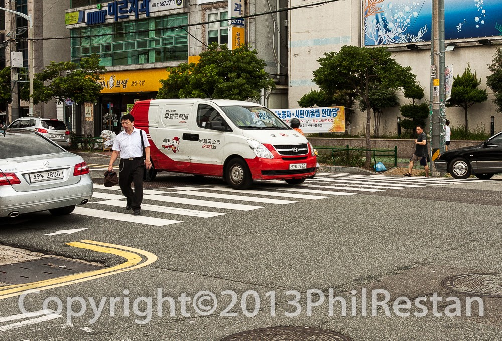 Image of man crossing at pedestrian crossing while cars drive around him in Korea