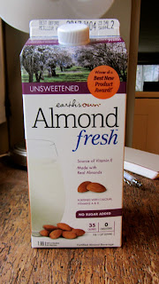 Container of Almond fresh milk on a wood table