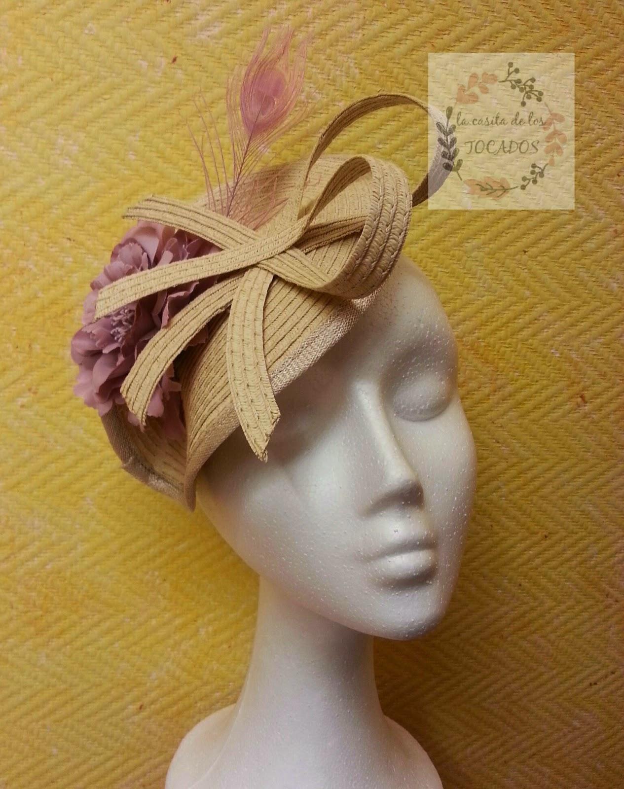tocado con base de paja sintética en color natural o beige, con adornos del mismo material a modo de lazo, flor clavel y pluma de pavo real