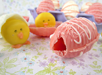 pink chocolate easter egg with crack and a baby chick mini oreo behind on flower surface