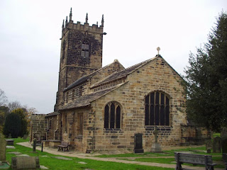 Stonebuilt church with square tower at the far end, so looking at it from the east.  Aisle to the south, but not on the north.  Benches and gravestones in the foreground.