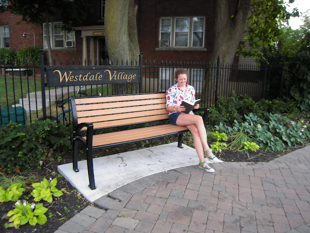 Blogger enjoying a good book on a bench in front of the Westdale Village sign.