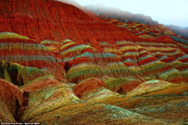 These incredible landscapes look as if they have been painted in the sweeping pastel brush strokes of an impressionistic artwork. But in fact these remarkable pictures show the actual scenery of Danxia Landform at Nantaizi village of Nijiaying town, in Linzhe county of Zhangye, Gansu province of China. Formed of layers of reddish sandstone, the terrain has over time been eroded into a series of mountains surrounded by curvaceous cliffs and unusual rock formations.