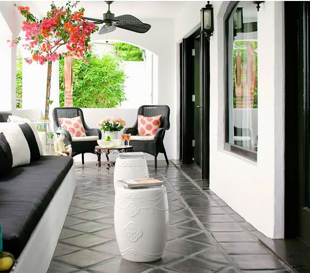Black and white patio with black wicker furniture with white cushions and pink accent pillows, a built in bench with black cushions and a tile floor