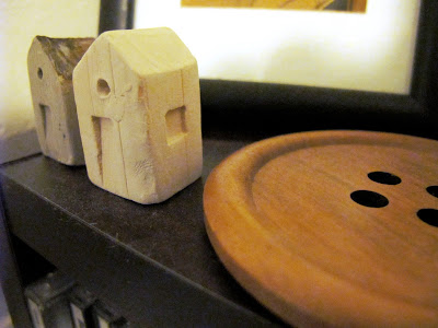 Two tiny pottery houses on display next to a giant wooden button.