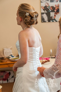 Bride getting resdy for her wedding witha messy loose bun hairstyle and vintage combs