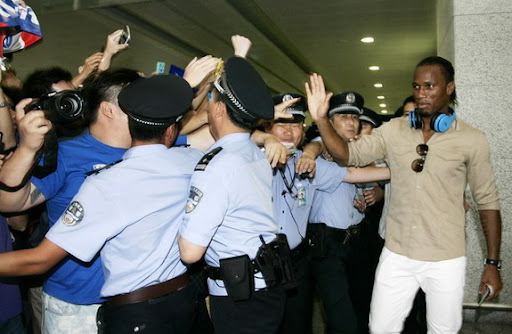 Former Chelsea star Didier Drogba waves to his fans upon his arrival in Shanghai