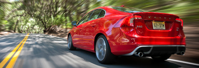 Rear 3/4 view of red 2012 Volvo S60 T6 AWD R SR being driven on two lane road