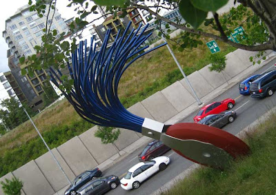 Giant typewriter eraser with round rubber disc and brush overlooking a stream of traffic below