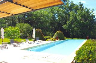 La piscine à débordement, 17 mètres de long sur 5 mètres de large, bains de soleil, parasols et coffre à serviettes de bain