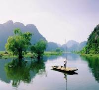Człowiek pływający tratwą po jeziorze w Wietnamie.