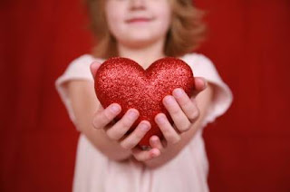 littl girl holds out sparkly heart
