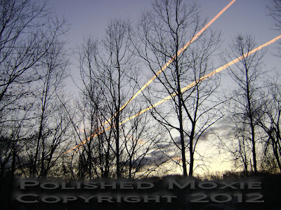 Colorful jet trails in the sky during a sunrise.