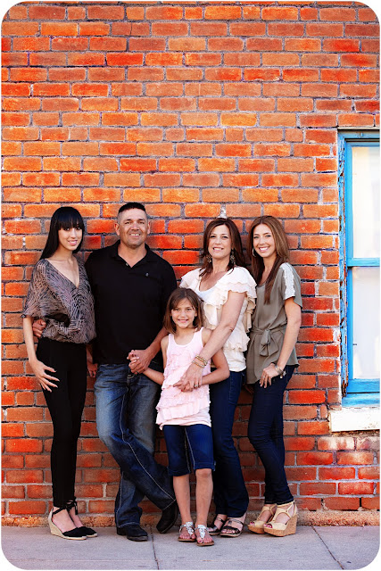 Beautiful family of five standing in front of brick wall in an urban setting