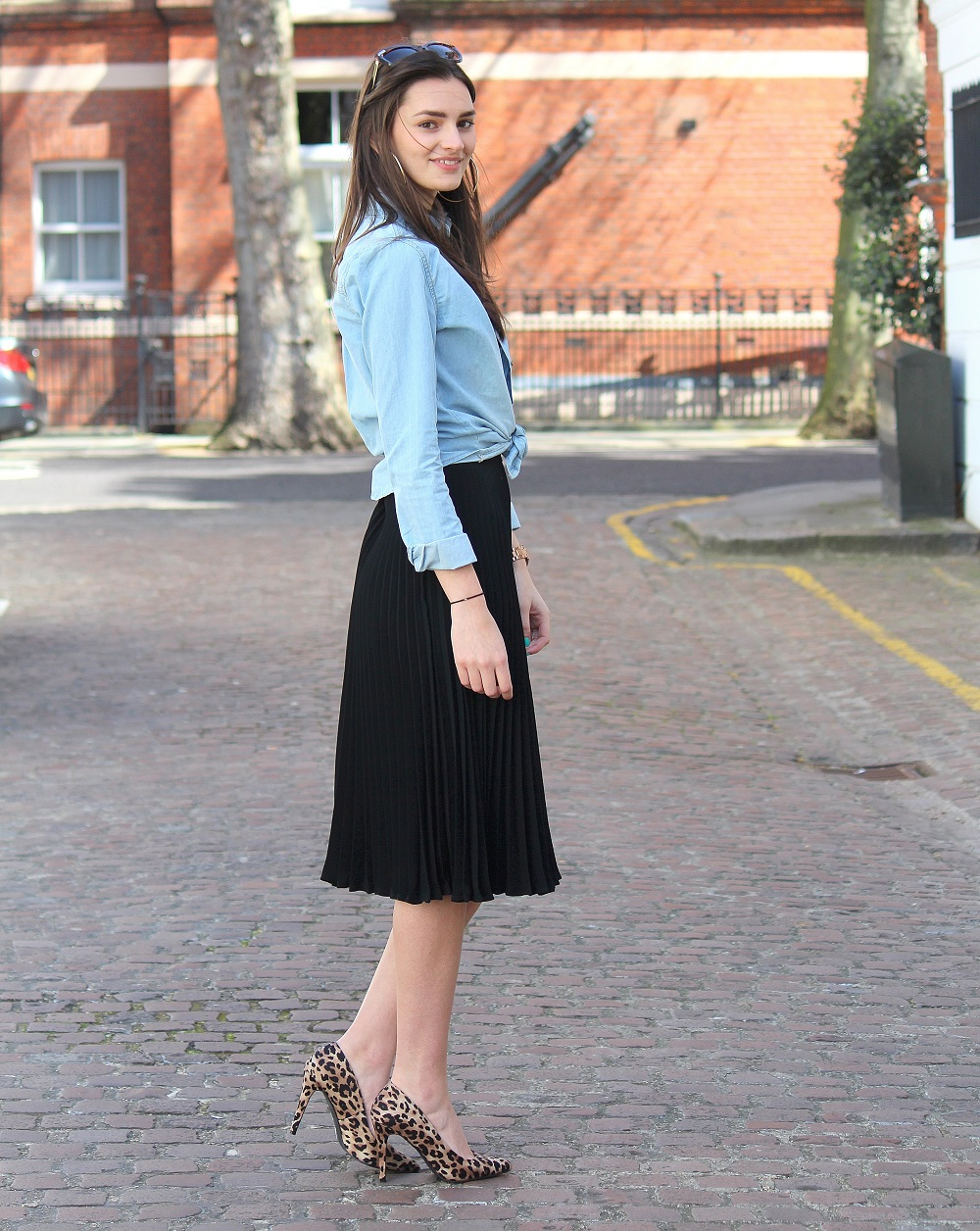 peexo fashion blogger wearing pleated midi skirt with lace bralet and denim shirt and leopard print heels and sunglasses in spring