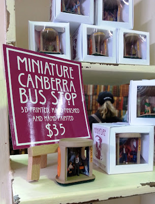 Stack of boxed model Canberra bus stops on a market stall.