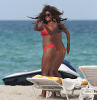 Claudia Jordan pointing at something on the beach