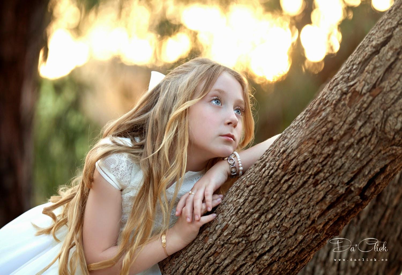 Retrato de niña de comunión en exterior, apoyada en arbol mirando al horizonte