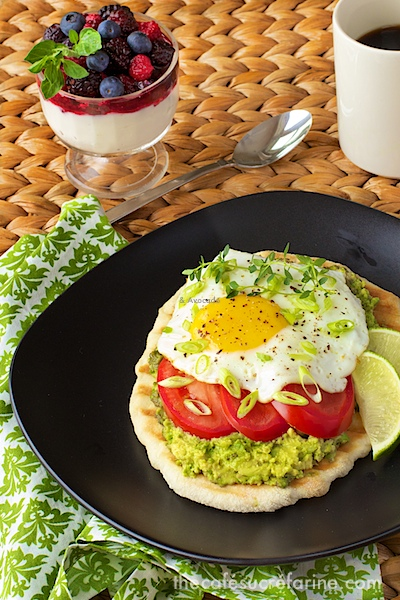Photo of a plate of Avocado Breakfast Flatbreads on a wicker table with a green and white napkin underneath the plate.