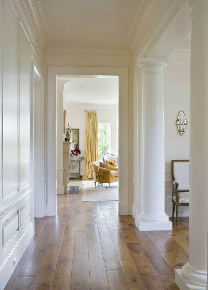 hallway in a san francisco mansion with  wide plank wood floors and greek columns