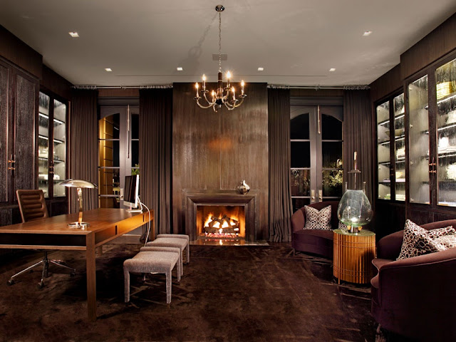 home office with dark wood paneling, brown brass chandelier, wooden desk and two brown armchairs