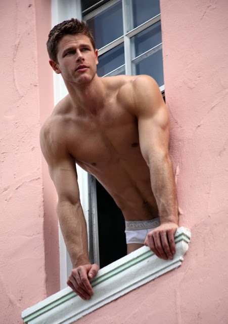 hot shirtless guy looking out of window