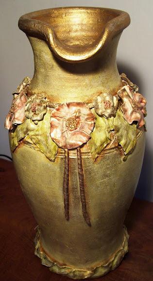 Reutilización, reciclado de un recipiente barro cocido roto, con flores y hojas en masilla epóxi. Frontal.