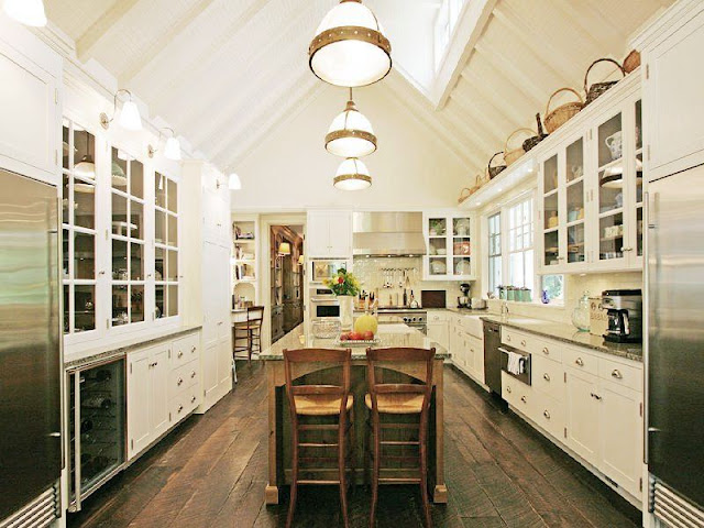 kitchen with a frame high ceiling, a skylight, rustic wood floors, white cabinets with glass upper cabinetry, a large island and stainless appliances