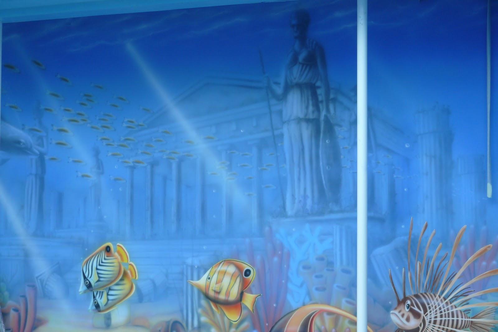 Artystyczne malowanie ściany na basenie, mural przedstawiający rafę koralową i rybki.